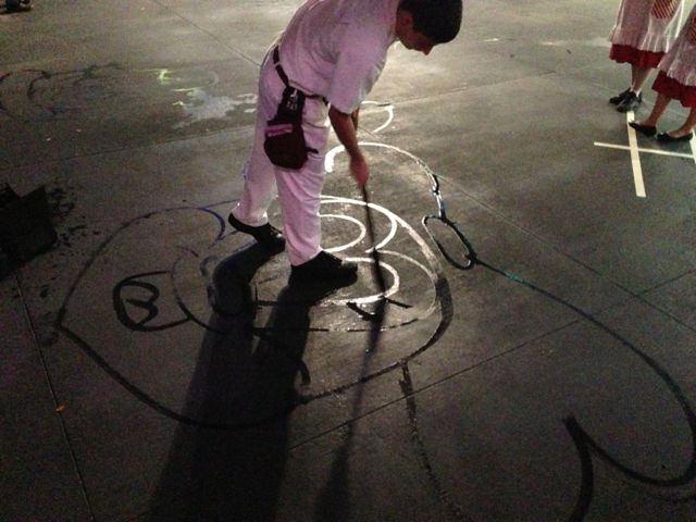 Disney janitor painting character on sidewalk with water and broom