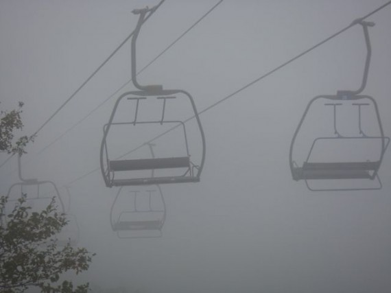 empty ski lift chairs in New York mountains's fog