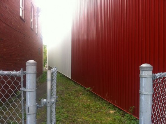random, photo of two red buildings and a fence gate
