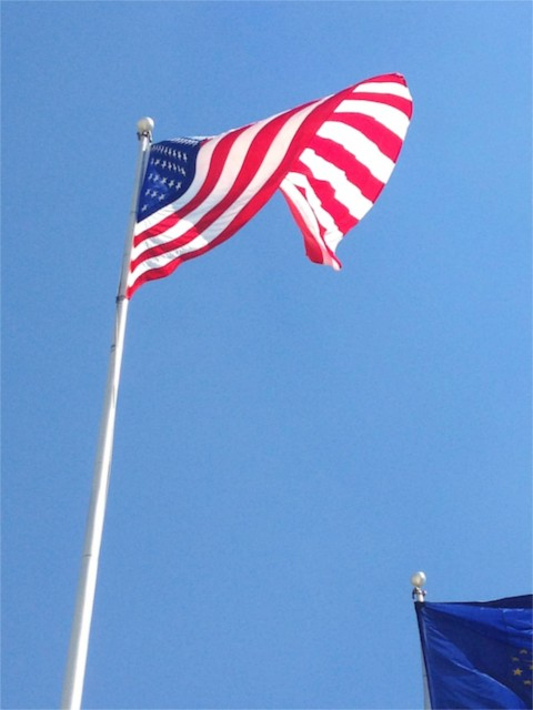 American flag blowing in the wind against a bright blue sky