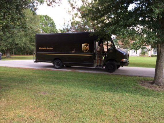 UPS delivery truck driver stepping off truck