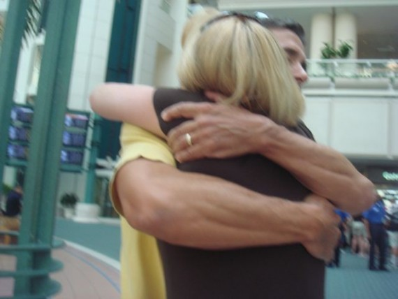 Husband and wife hug at airport