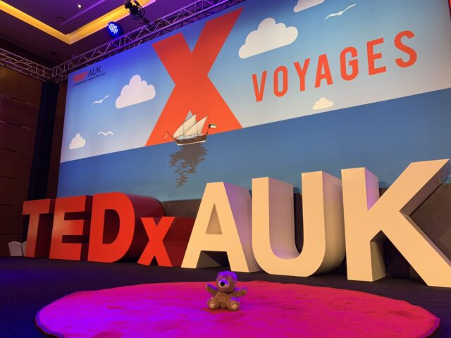 TEDx stage with teddy bear on red dot