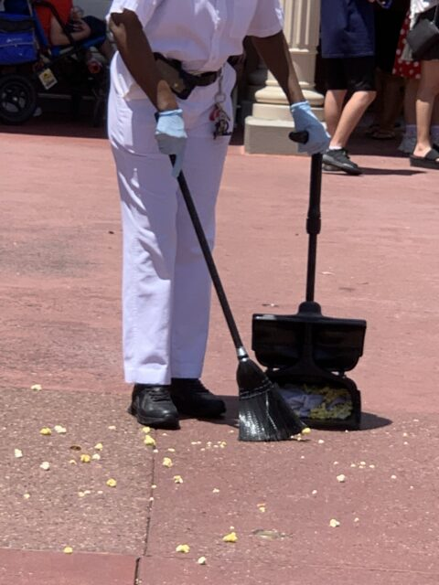 Disney custodial cast member with apan and broom