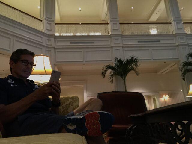 man using phone in hotel lobby