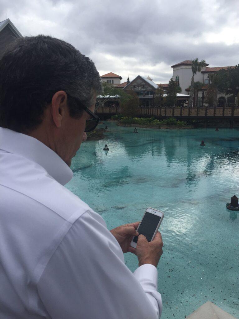 Disney customer service author Jeff Noel writing on iPhone