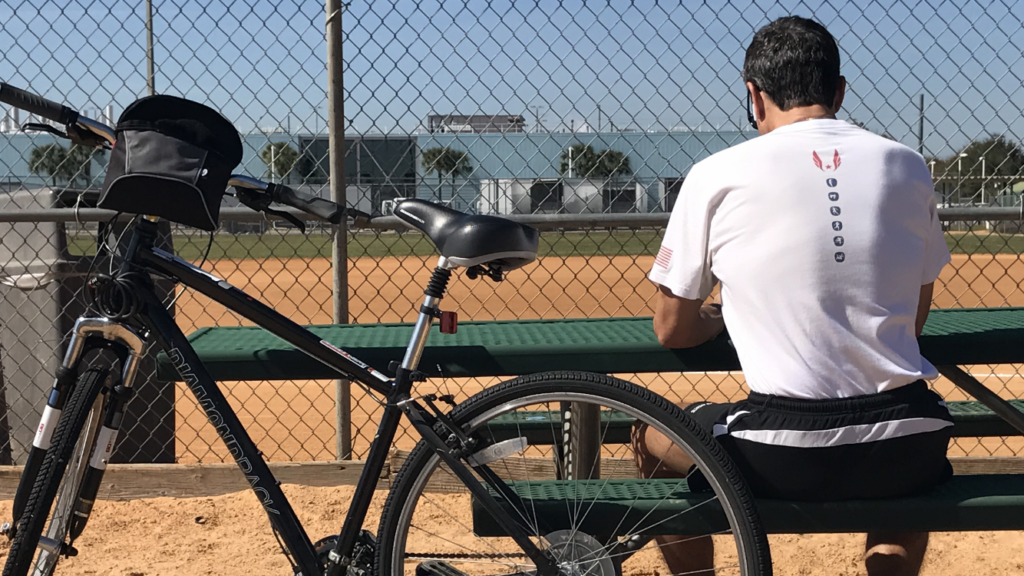 Man with back turned, sitting next to bicycle